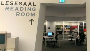 Im Vordergrund eine Wand mit der Aufschrift »Lesesaal«, im Hintergrund Bücherregale und Lesetische