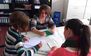 Drei Webredakteurinnen sitzen um eine Tisch und diskutieren
