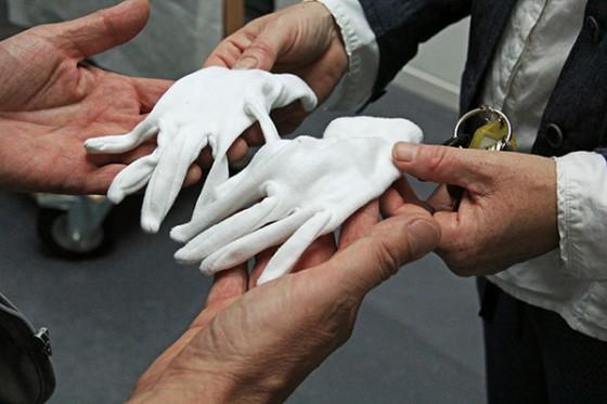 Vier Hände und ein Paar weiße Handschuhe