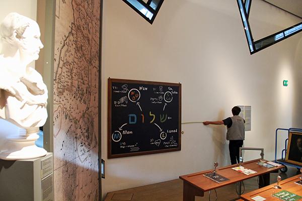 Raum mit hölzernen Schulbänken und einer Tafel an der Wand