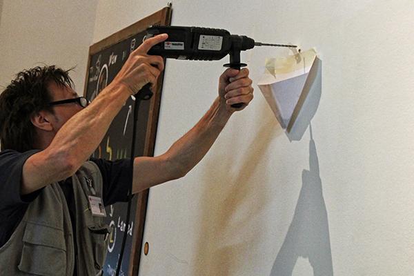 Ein Mann hält eine Bohrmaschine an die Wand, unter dem Bohrloch hängt eine gefaltete Papiertüte