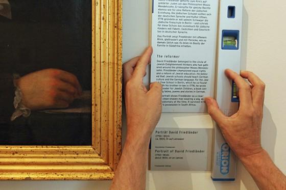 Neben dem Gemälderahmen wird eine Wasserwage an eine Hinweistafel gehalten