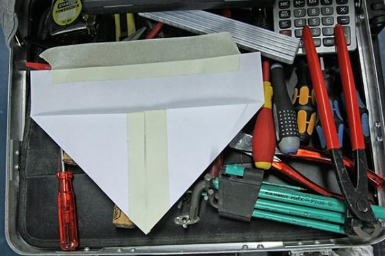 Werkzeugkasten auf dem eine gefaltete und verklebte Papiertüte liegt