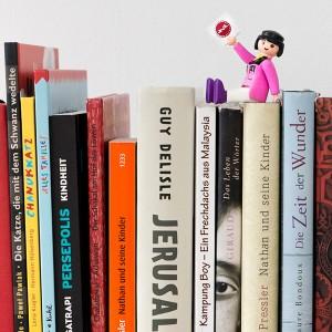 Verschiedene Buchrücken, auf denen eine Playmobilfigur mit dem Logo des Jüdischen Museums Berlin in der Hand sitzt