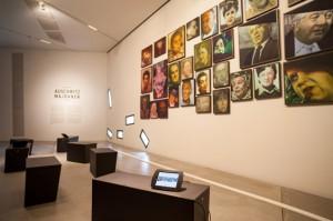 44 Portraits hängen an der Wand, davor schwarze Bänke, auf denen iPads liegen