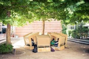 Holzhütten in einem Kreis auf dem Schulhof, die Schüler sitzen darin