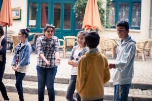 Schülerinnen und Schüler stehen in einem lockeren Kreis und tauschen sich aus
