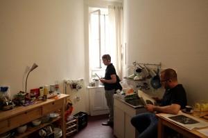Ein Teilnehmer mit Kopfhörern steht konzentriert und mit Blick auf einen Zettel vor dem Küchenfenster, eine andere Person sitzt am Tisch und liest etwas