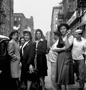 Schwarz-Weiß-Foto, auf dem mehrere Frauen auf einer Straße stehen und den Betrachter ansehen