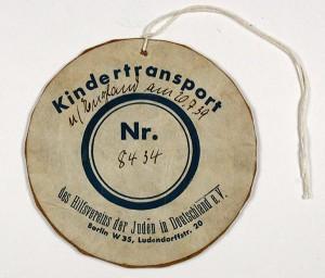 rundes Schild mit der Aufschrift »Kindertransport«, in der Mitte eine Nummer
