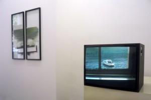 Ausstellungsansicht, links Glasrahmen, rechts Fernseher mit Bild vom Meer