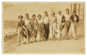 Neun Menschen untergehakt in einer Reihe am Strand entlang laufend