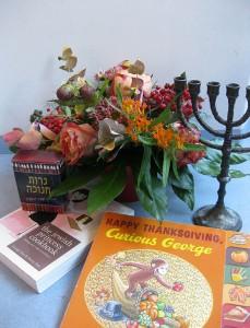 Eine Menora, ein Blumenstrauß und das Buch »Curious George«