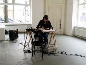 Foto der Künstlerin, sie sitzt an einem Schreibtisch in in einem ansonsten fast leeren Raum