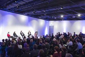 Ein gefüllter Saal mit fünf Diskutierenden auf dem Podium