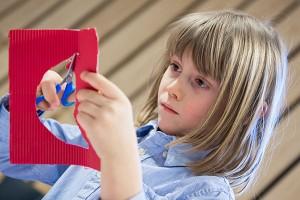 Ein Mädchen schneidet mit einer Schere etwas aus einem roten Karton aus.