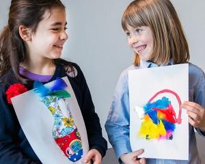 Zwei Mädchen zeigen sich lächelnd ihre Entwürfe einer Vase und einer Teekanne.