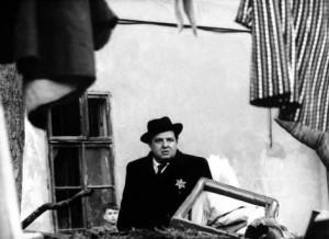Filmstill, Mann mit Hut vor einem Haus