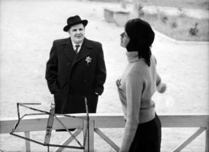 Filmstill, Mann mit Hut schaut zu einer Frau hinauf, neben ihr ein Notenständer