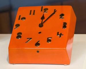 Orange glasierte, quadratische Uhr mit schwarzen Ziffern