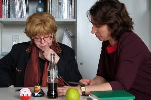 Zwei Frauen an einem Tisch betrachten ein ihnen vorliegendes Papier