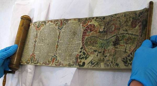 Hände in blauen Handschuhen rollen eine Schriftrolle mit hebräischen Buchstaben und farbigen Illustrationen aus.