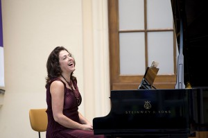 A laughing woman sitting at a piano