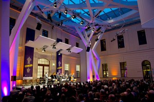 Musicians on the stage in a glass-covered courtyard in front of an audience