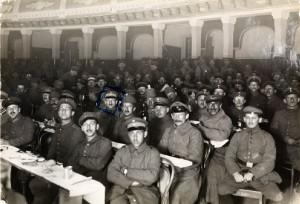 Zuschauerreihen eines Theatersaals besetzt mit Männern in Uniform