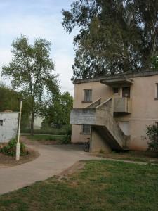 Zweistöckiger Bungalow mit Außentreppe, dahinter Bäume