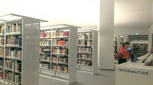 Eine Lesesaalbesucherin informiert sich beim Bibliothekar am Informationspult.