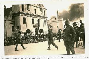 Schwarz-weiß Fotografie von einer Kirchenfassade vor der Menschen auf dem Boden sitzen, im Vordergrund deutsche Soldaten
