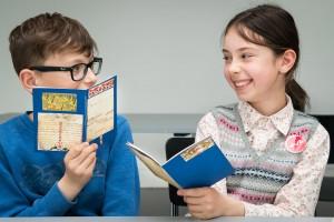Ein Junge und ein Mädchen zeigen sich gegenseitig selbst gebastelte Büchlein