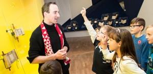 Ein Museumsführer mit einer Gruppe Kinder in der Ausstellung »Die Erschaffung der Welt«, ein kleiner Junge meldet sich