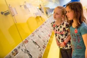 Zwei Mädchen vor Ester-Rollen in einer Vitrine an einer gelben Ausstellungswand