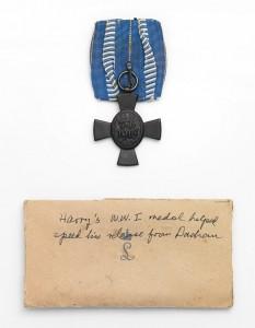 Kreuz am weiß-blauen Band, darunter ein Umschlag mit der Aufschrift »Harry's WWI medal helped speed his release from Dachau«