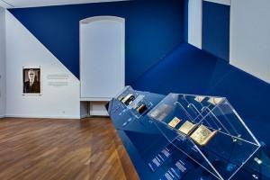 Ein Raum in dunkelblauer und weißer Farbe gestrichen. Auf dem hellen Holzfußboden sind schräge, blaugehaltene Wände angebracht auf denen Bücher in Glasvitrinen besfestigt sind