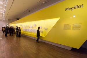 Personen stehen in einem gelb gestrichenen Raum vor einer sehr langen Galsvitrinen, die auf der rechten Seite in eine gelbe Ausstellungsfläche eingearbeitet wurde. In der Vitrine hängen verschiedenen Schriftrollen.