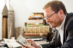 Ein Mann sitzt an einem Tisch und hält ein aufgeschlagenes Buch in den Händen