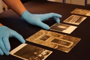Hände in blauben Handschuhen rücken schwarz-weiß Fotografien auf schwarzem Stoff zurecht.