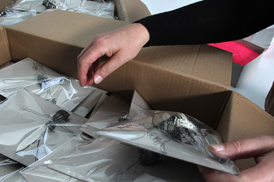 In Plastik verpackte kleine Figuren aus Gleisschotter und Draht