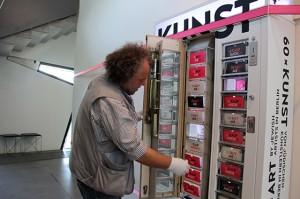 Ein Mann mit weißen Handschuhen zieht an einem Fach des Kunstautomaten