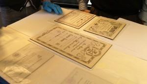 Die Urkunde und weitere Papiere liegen auf einem weißen Tisch, auf dem sich eine Hand in blauem Handschuh abstützt.