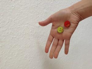 Die zwei Knöpfe werden auf der Handfläche liegend gezeigt