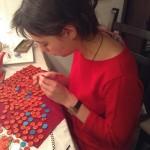 Die Künstlerin beschriftet die vielen Knöpfe, die vor ihr auf dem Tisch liegen