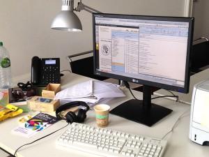 Ein Schreibtisch mit PC Bildschrim, Tastatur, Büchern und einer Kaffeetasse