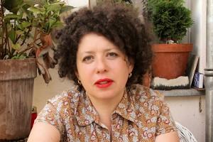 Portraitaufnahme einer Frau mit rotem Lippenstift und schwarzen langen Locken. Sie sitzt auf einem Balkon schaut direkt in die Kamera.