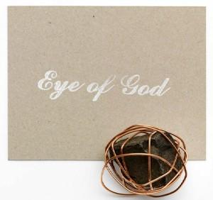 """Ein mit draht umwickelter Schotterstein liegt neben einer grauen Karte auf der mit weißer Schrift """"Eye of God"""" steht"""