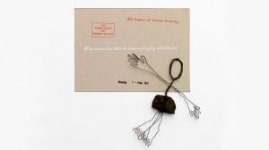 Eine Figur aus Draht und Schotterstein liegt neben einer grauen Karte