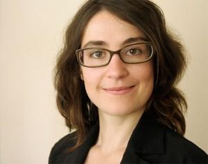 Portraitaufnahme einer Frau mit schwarzer Brille, schwarzer Kleidung und langen braunen Haaren vor einer weißen Wand